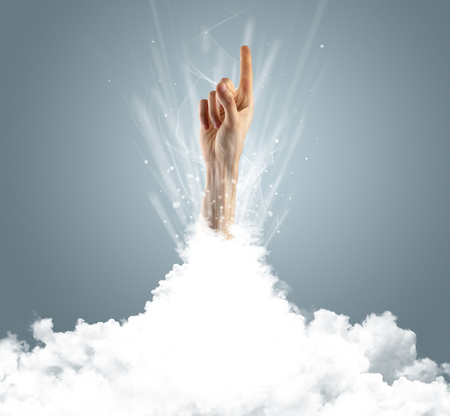 Hand breaking out from cloud Stock Photo