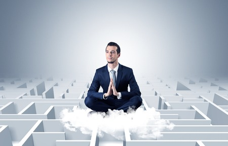 Young businessman meditate in yoga position on a cloud with infinity maze concept Reklamní fotografie
