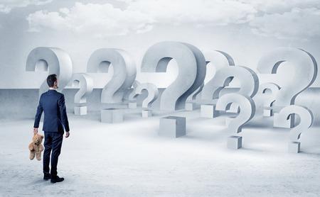 Empresario de pie y mirando a un montón de signos de interrogación