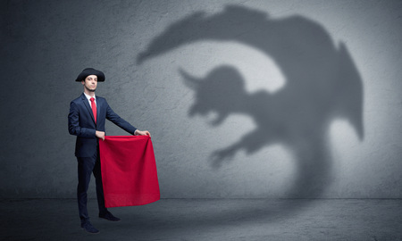 Businessman standing with red cloth in his hand and imp shadow on the background Reklamní fotografie