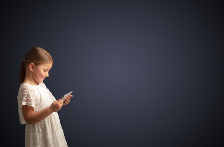 Adorable little girl using tablet with dark empty space Stock Photo