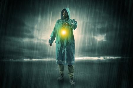 Hombre impermeable caminando en tormenta con linterna brillante en la mano