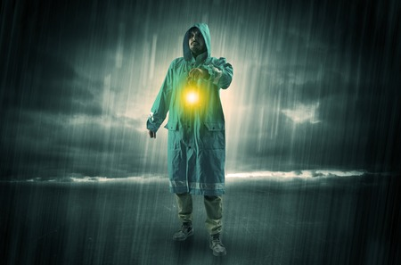 Raincoated man walking in storm with glowing lantern in his hand