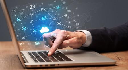 Zakenmanhand die een heleboel berichten op laptop verzendt met cloud computing-concept Stockfoto
