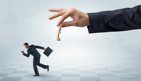 Small frail businessman with suitcase running away from big hand with chessman concept Фото со стока