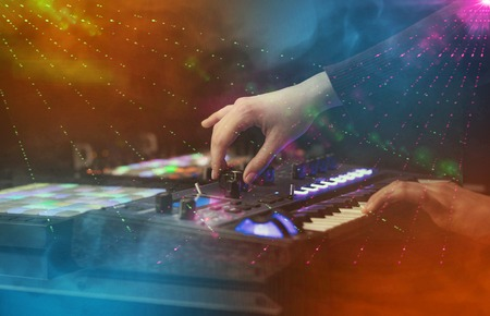 Hand mixing music on midi controller with party club colors around