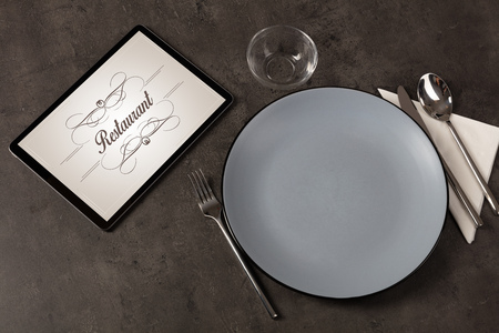 Tablet with stylish restaurant logo and laid table