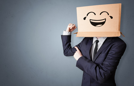 Funny man wearing cardboard box on his head with smiley face Imagens
