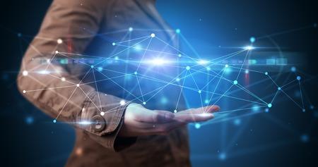 Persona hermosa que sostiene la pantalla del holograma que muestra la tecnología moderna del sistema web basado en la nube Foto de archivo