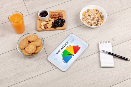 Healthy food with tablet on a wooden background with words Body Mass Index. Health concept.