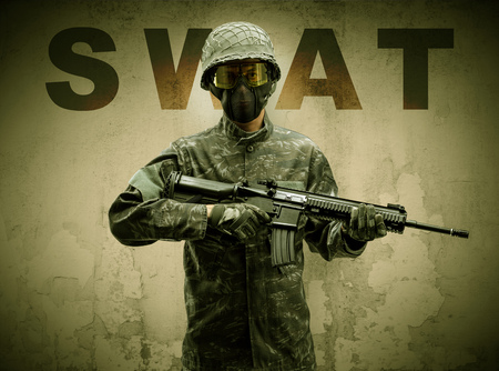 Uniformed armed soldier with damaged wall background Stock Photo