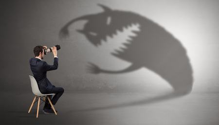 Young businessman staying and  negotiate with a monster shadow Stock Photo