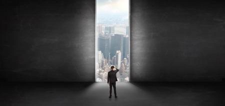 Geschäftsmann, der in einem dunklen Raum steht und nach draußen zu einer Stadtbildansicht schaut Standard-Bild
