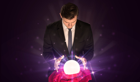 Young businessman sitting with crystal ball in action Stock Photo