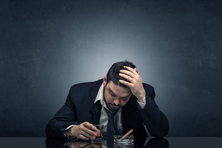 Young drunk man at his office with free dark copyspace Stock Photo