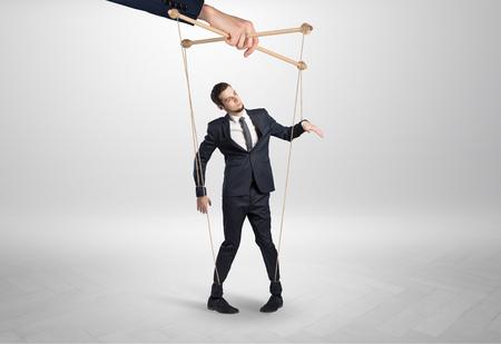 Marionet zakenman in een lege kamer geleid door een enorme hand