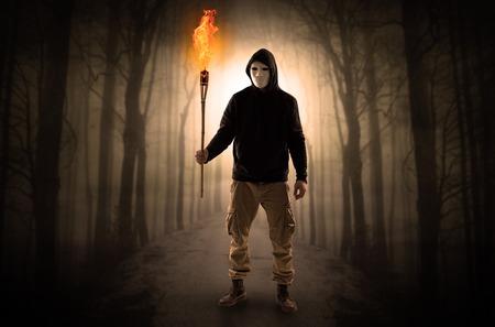 Mysterieuze man die van een pad in het bos komt met een brandend flambeau-concept