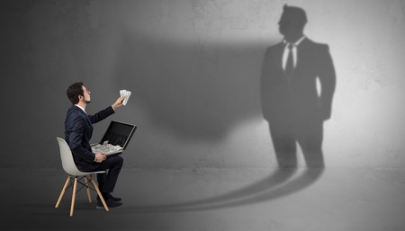 Humble businessman staying and offering stuffs to a huge businessman shadow Stock Photo - 123348797