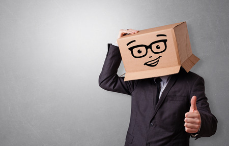 Handsome man standing and gesturing with a carton box on his head