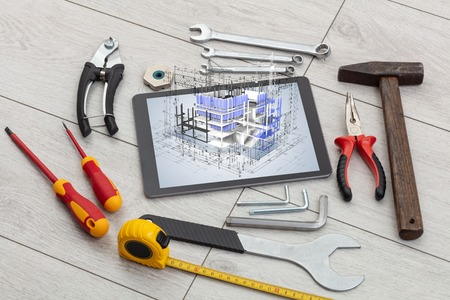Tablet with construction tools and 3d house plan concept