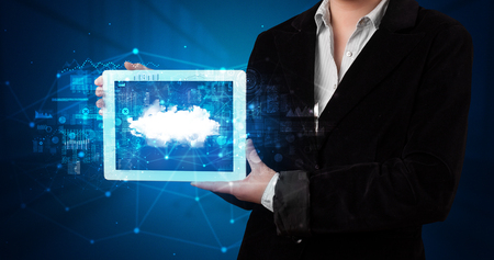 Hand holding tablet with cloud technology and dark concept