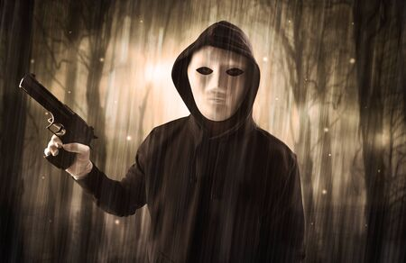 Masked armed hitman in dark thick forest with foggy mysterious concept