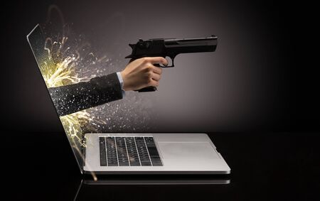 Hand with gun coming out of a laptop with sparkling effects Imagens