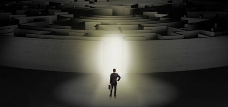 Businessman getting ready to enter a concentric labyrinth with lighted entrance concept