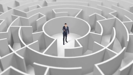 Young businessman standing in a middle of a 3d round maze 写真素材