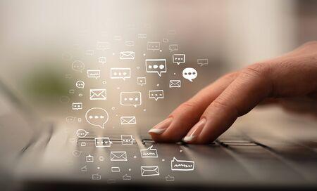 Zakenvrouw hand typen op toetsenbord met chat-pictogrammen rond