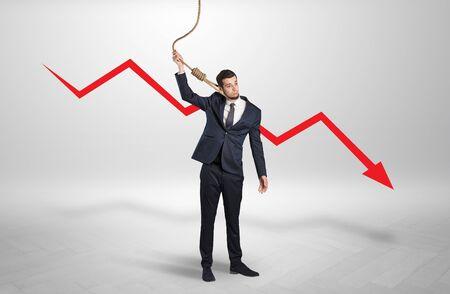 Concept of stressed businessman with arrow declining behind him Reklamní fotografie