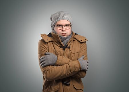 Handsome young boy freezing in warm clothing with copy space
