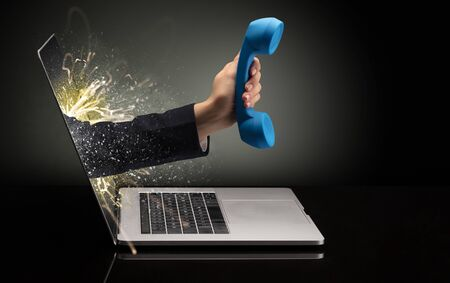 Hand with phone coming out of a laptop with sparkling effects Imagens