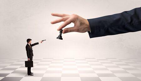 Kleinunternehmer, der auf einer großen Hand mit Schachbrettkonzept gegen große Schachfiguren kämpft Standard-Bild