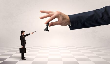 Small businessman fighting against big chessman on a big hand with chess board concept Stock Photo