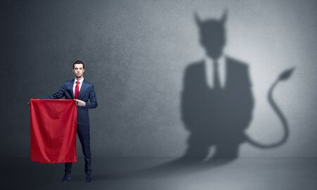 Businessman standing with red cloth in his hand and devil shadow on the background Standard-Bild