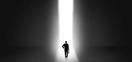 Businessman standing and seeing the light at the end of a big wall Reklamní fotografie