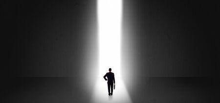 Homme d'affaires debout et voyant la lumière au bout d'un grand mur Banque d'images