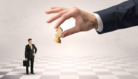Small businessman fighting against big chessman on a big hand with chess board concept Фото со стока