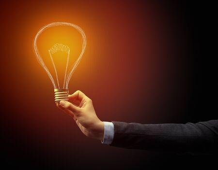 Hand, die Glühbirne auf dunklem Hintergrund hält. Neues Ideenkonzept