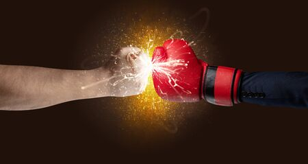 Two hands fighting with orange dust, spark, glow and smoke concept