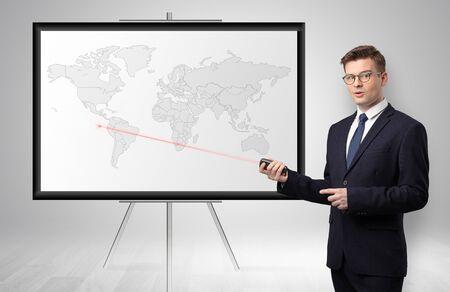 Apuesto hombre de negocios con puntero láser que presenta área comercial potencial en el mapa Foto de archivo