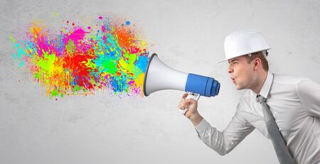 Young architect constructor yelling with megaphone with and colorful splash concept Foto de archivo