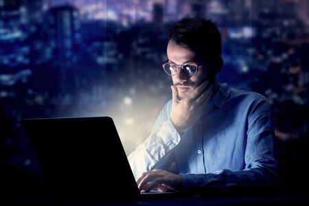 Young handsome businessman working late at night in the office with blue lights in the background Standard-Bild