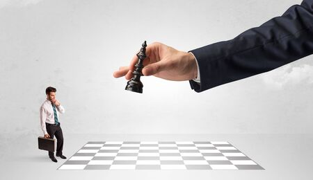 Little businessman thinking about chess strategy with a big hand concept