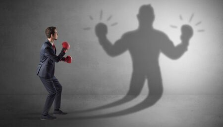 Businessman trying to fight with his unarmed shadow