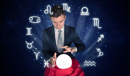 Young handsome astronaut looking for inspiration in his crystal magic ball