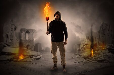 Destroyed place after a catastrophe with man and burning flambeau concept Reklamní fotografie