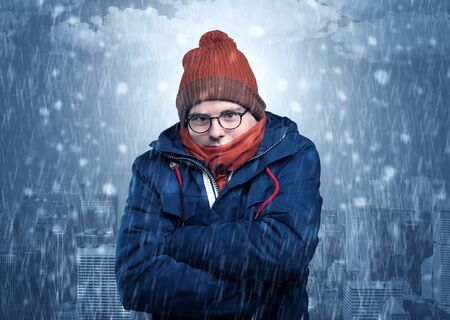 Young man freezing in warm clothing with city concept Standard-Bild