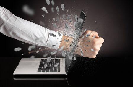 Strong male hand breaks laptop screen Stock Photo